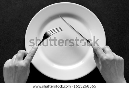 Fork and knife in hands black and white. Royalty-Free Stock Photo #1613268565