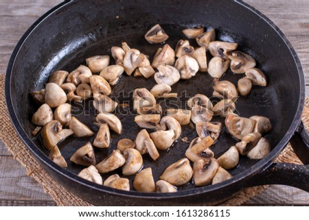 Fried mushrooms in frying pan on wooden table #1613286115