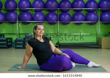 Overweight woman overweight doing fitness with ball. Obese blonde is resting after a productive workout in the gym. #1613314840