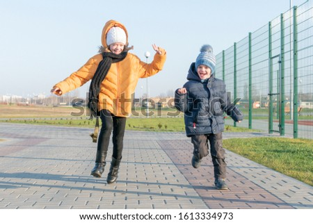 Teenage girl with younger brother walking in the new Park