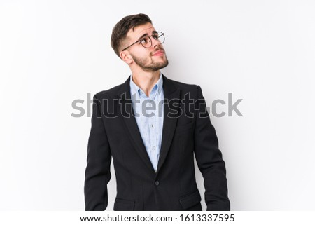 Young caucasian business man posing in a white background isolated Young caucasian business man dreaming of achieving goals and purposes #1613337595
