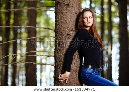 Beautiful young woman leaning on a tree in a forest #161334971