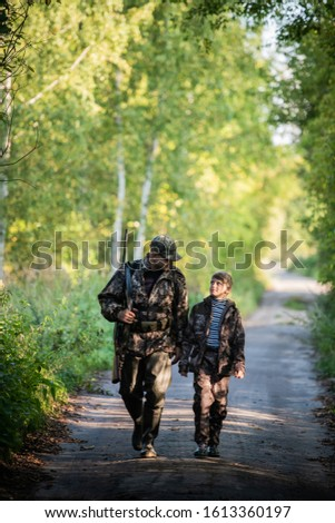 Father and son together hunting together. Walking the road in a forest. #1613360197