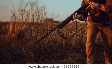 Hunter's hands holding a gun. Man standing outdoors and wearing checkered shirt, camel pants, leather ammunition belt and smart watch. Photo with selective focus