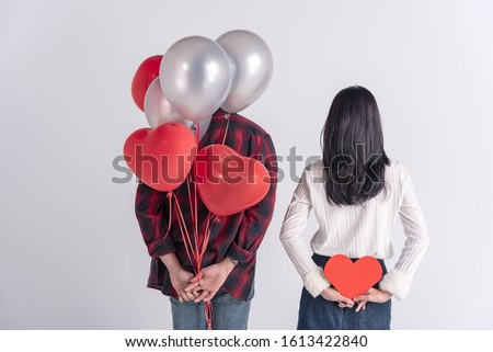 Beautiful Young asian couple at home,enjoy spend time together in celebration Saint Valentine's day,hand hold balloon,cartoon paper red heart,happy and love motion.