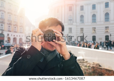 Young Asian man tourist taking photos with camera in hands near Hofburg palace in Vienna, Austria, Europe. Famous popular touristic place in Europe #1613467087
