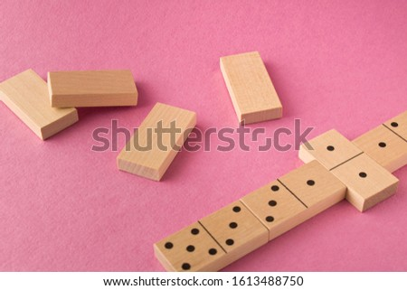 Playing dominoes on a purple background. Leisure games concept. Domino effect #1613488750