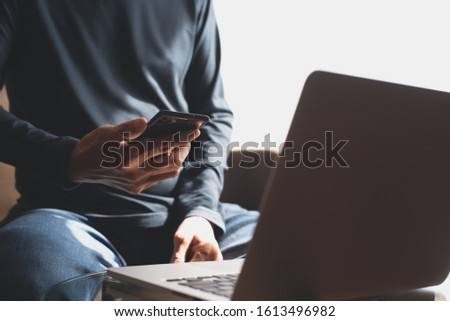 Casual business man using mobile phone with laptop computer on table at home office. Freelancer online working on laptop, connecting internet via smartphone, close up #1613496982