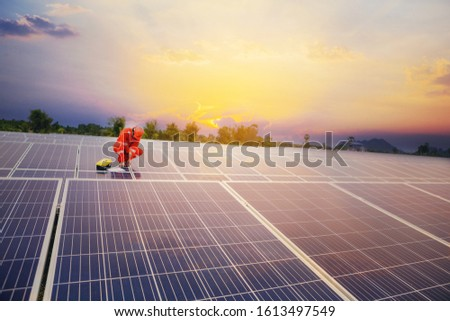 Electrical and instrument technician use wrench to maintenance electric system at solar panel field with sunset sky #1613497549