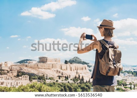 Young woman taking photographs with smart phone in Athens with Acropolis at the background. Traveler girl enjoying vacation in Greece. Summer holidays, vacations, travel, tourism, technology concept. #1613536540