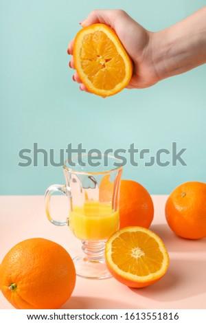 Creative and fashionable photo, pastel colors. Female hand crushes orange, juice. #1613551816