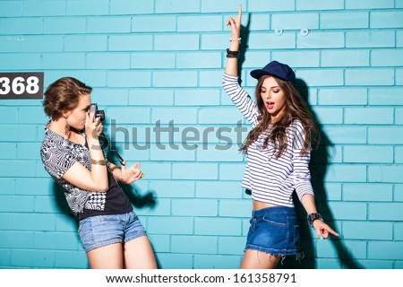a girl takes picture of her friend in front of light blue brick wall