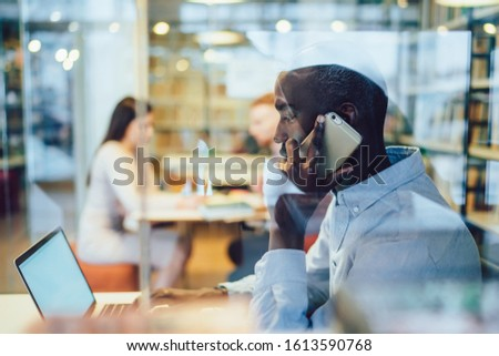 Side view of black man in blue shirt answering phone call and browsing laptop with empty screen white sitting at table behind glass in library #1613590768