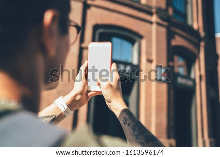 Cropped image of millennial hipster traveller making pictures of building on urban setting connected to online application and 4g internet for posting media publications, selective focus on cellphone #1613596174