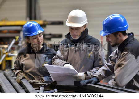 Apprentice working in steelworks plant, with instructor #1613605144