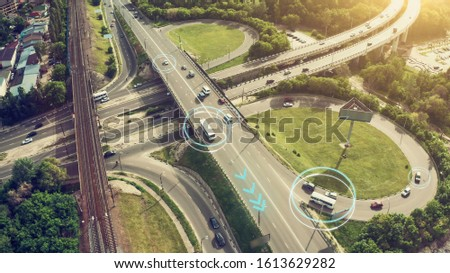 Autonomous Self Driving Cars Concept. Aerial view of cars and buses moving on city intersection and Artificial Intelligence scans road with sensors and control vehicles in traffic #1613629282