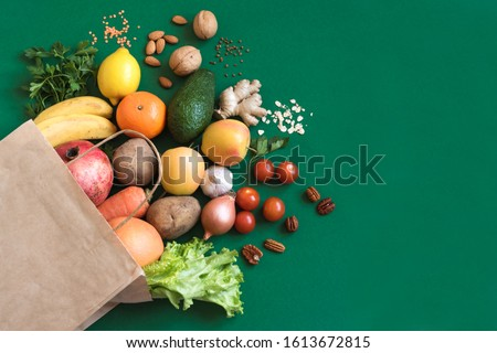 Healthy food background. Healthy vegan vegetarian food in paper bag vegetables and fruits on green, copy space. Shopping food supermarket and clean vegan eating concept. #1613672815