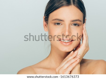 Beauty woman face healthy skin natural makeup hand touching face female model #1613676373