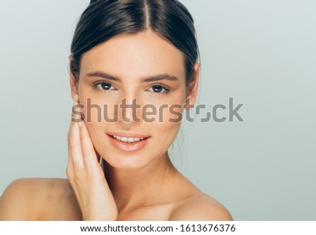 Beauty woman face healthy skin natural makeup hand touching face female model #1613676376