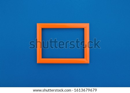 Empty orange frame on the classic blue background. Trendy greeting card. Minimal concept. Copy space for your text. Flat lay style. Top view.
