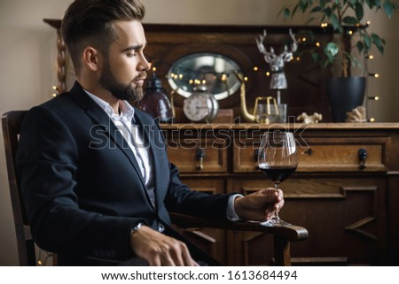 Portrait of handsome bearded man with a glass of red wine #1613684494