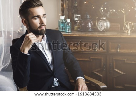 Portrait of handsome bearded man wearing black classic suit #1613684503