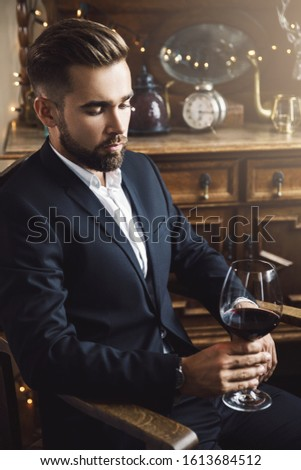 Portrait of handsome bearded man with a glass of red wine #1613684512
