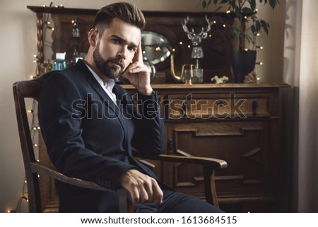 Portrait of handsome bearded man wearing black classic suit #1613684515