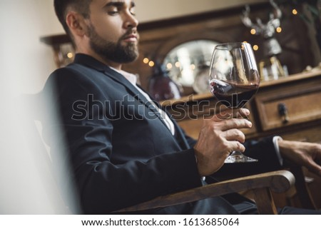 Portrait of handsome bearded man with a glass of red wine #1613685064