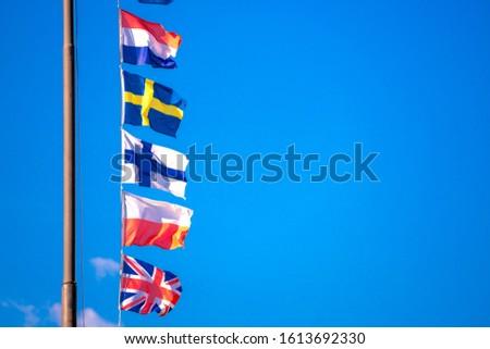 Various European flags waving on tall flagpole against blue sky on sunny day #1613692330