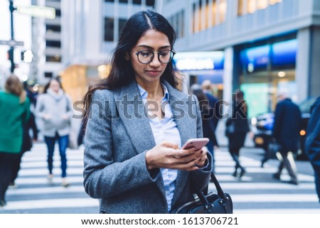 Young attractive business woman wearing shirt and gray jacket using mobile phone while crossing road in New York City on daytime #1613706721