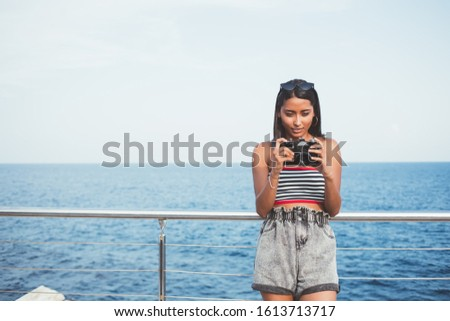 Front view of attractive millennial tourist checking photo images on modern technology standing near ocean during summer vacations, beautiful hipster girl editing pictures on advanced SLR camera