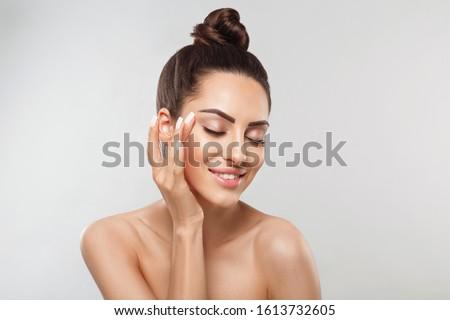 Beautiful smiling woman with healthy smooth facial clean skin applying cosmetic cream and touch own face. Model with  Beauty face. Skin care Moisturizer Facial treatment. Cosmetology. Spa. #1613732605
