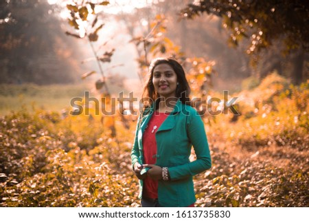 An young and attractive brunette Indian Bengali woman in winter jacket in grass field in winter afternoon in natural forest background. Indian lifestyle,winter, fall colors and back light photography #1613735830