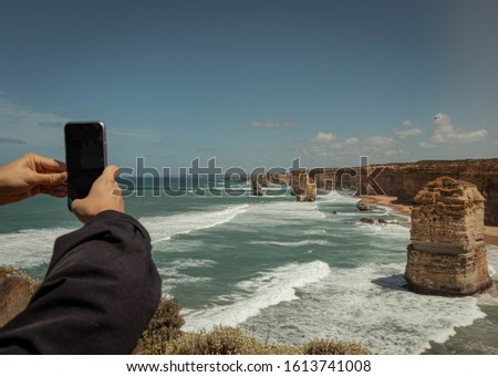 Tourist taking pictures of scenic 12 apostles rock formations and cliffs in australia