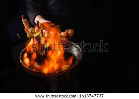 Professional cook cooks shrimps with vegetables on fire. Cooking seafood, healthy vegetarian food, roasting over an open fire. on a dark background. Hotel service, oriental cuisine asia food #1613747737