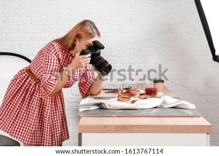 Young woman taking picture of pancakes in professional studio