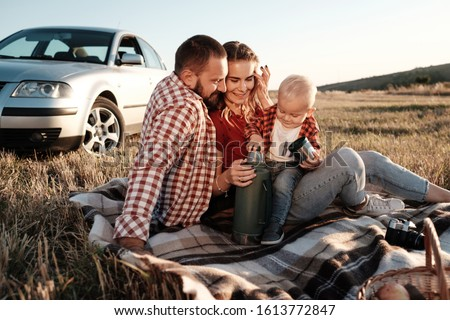 Happy Young Family Mom and Dad with Their Little Son Enjoying Summer Weekend Picnic Sitting on the Plaid Near the Car Outside the City in the Field at Sunny Day Sunset, Vacation and Road Trip Concept #1613772847