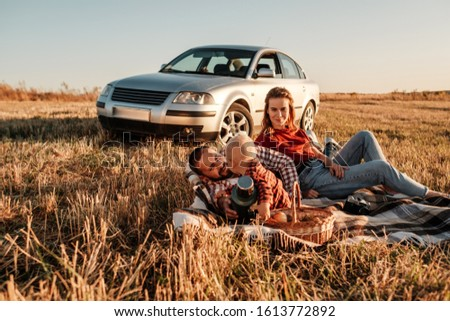 Happy Young Family Mom and Dad with Their Little Son Enjoying Summer Weekend Picnic Sitting on the Plaid Near the Car Outside the City in the Field at Sunny Day Sunset, Vacation and Road Trip Concept #1613772892