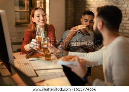 Small group of creative people having fun while toasting with beer and eating pizza in the office.  #1613774656