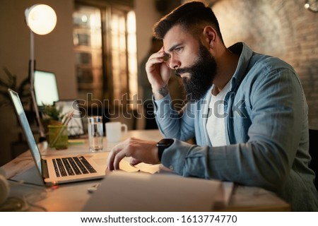Worried businessman reading an e-mail on a computer while working at night in the office.  #1613774770