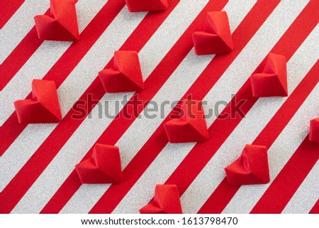 Pattern red origami hearts on red background with silver glitter stripes. Valentine's day holiday isometric backdrop #1613798470
