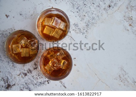 Three glasses filled with ice cubes and old aromatic whiskey placed on white rustical table #1613822917