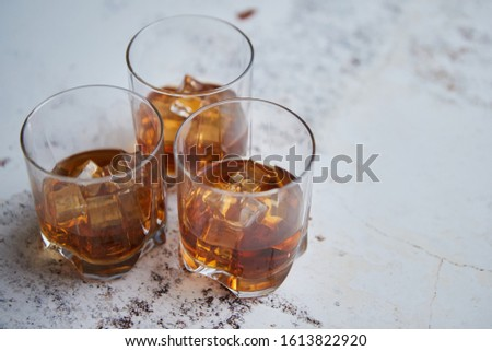 Three glasses filled with ice cubes and old aromatic whiskey placed on white rustical table #1613822920