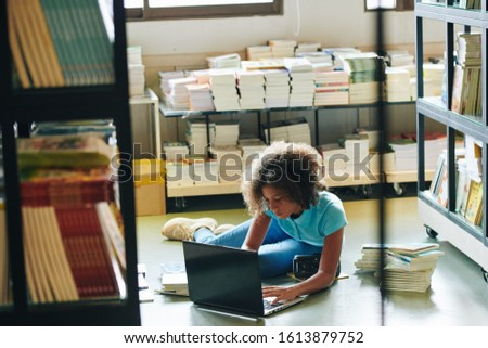 Teen girl of mixed race doing school project in library using laptop #1613879752