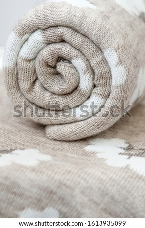 A rolled up knit plaids. The plaid has a pattern in the shape of white cotton boxes. Jacquard. #1613935099