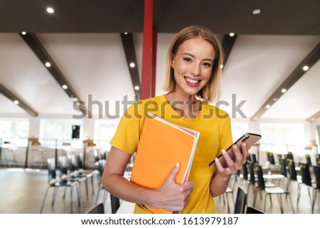 Photo of joyful young woman holding exercise books and cellphone while standing in open-plan office #1613979187