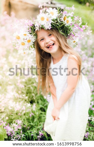 Cute smiling girl with flower wreath on a meadow on a farm. Mid summer. rubber boots . purple. smiles. laughs. Close up portrait of beautiful joyful blonde Caucasian girl smiling demonstrating white  #1613998756