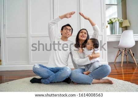 Positive young Asian married couple with infant boy looking up and making roof figure with hands while sitting on carpet in light room #1614008563