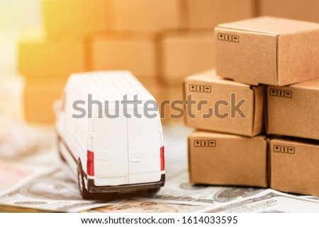 Cargo bus and a lot of cardboard boxes on a money background. Cargo Delivery Business Development Concept. #1614033595